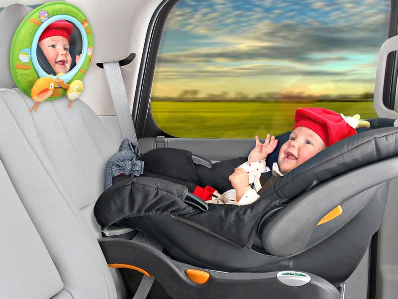 Baby In Car Seat With Mirror Attached To Headrest
