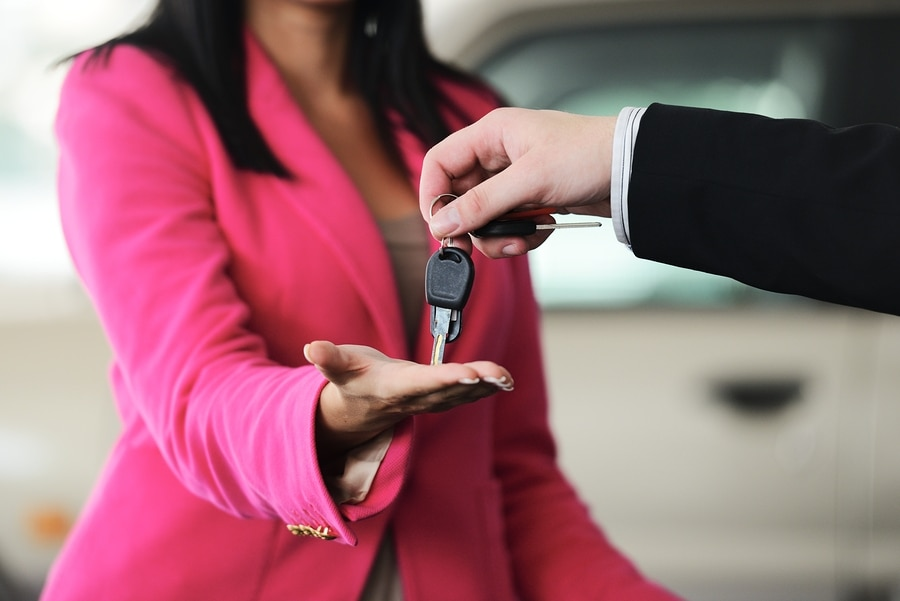 handing keys to black woman